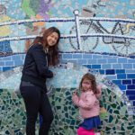 Claudia Latorre desinger with her little one in front of the ready mosaic