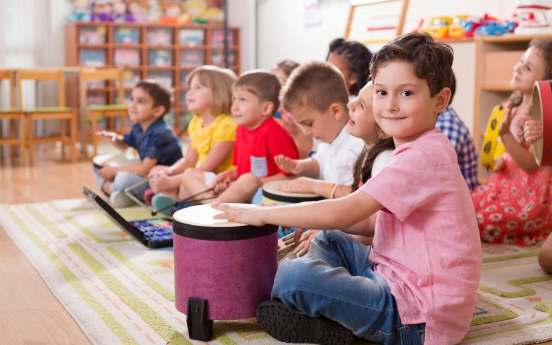 A group of pre-school boys and girls in a classroom.  They are participating in a music class.